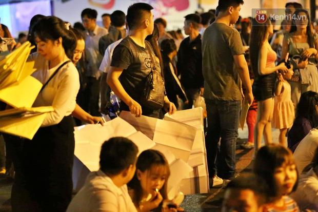 Hàng vạn người đổ về trung tâm chờ xem pháo hoa, các thánh tranh thủ ở Sài Gòn ăn nên làm ra nhờ bán giấy lót ngồi - Ảnh 3.