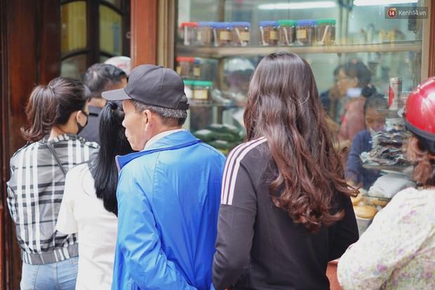 Người Hà Nội xếp hàng cả tiếng chờ mua bánh chưng, giò chả tại cửa hàng có tiếng chiều 29 Tết - Ảnh 2.