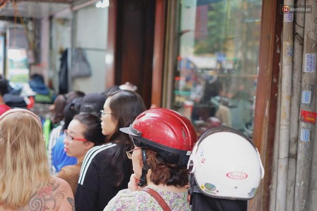 Người Hà Nội xếp hàng cả tiếng chờ mua bánh chưng, giò chả tại cửa hàng có tiếng chiều 29 Tết - Ảnh 4.