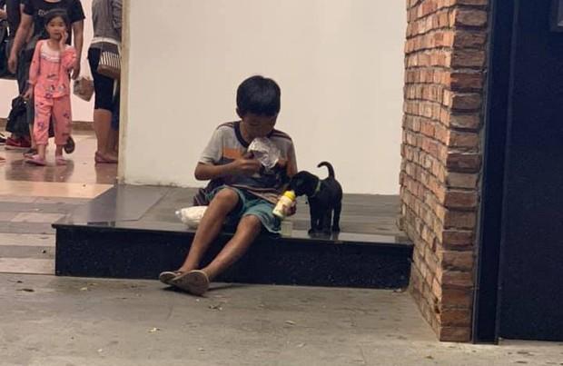 Hình ảnh xúc động: Chỉ có 1 gói sữa nhưng cậu bé san đôi, vừa uống vừa bón cho chú chó nhỏ trên vỉa hè - Ảnh 1.