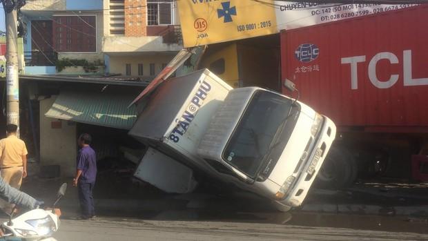 Tài xế vô tư say giấc trong cabin sau khi lái xe container tông sập 2 nhà dân - Ảnh 1.