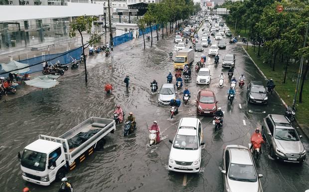 Mùa nóng chưa qua mùa ngập đã tới: Người Sài Gòn lại bì bõm lội nước về nhà sau cơn mưa lớn - Ảnh 2.