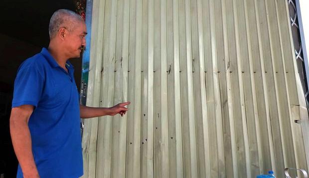 Côn đồ mang súng đến nhà bắn khiến 1 người bị thương, đạn găm chi chít trên cửa - Ảnh 2.