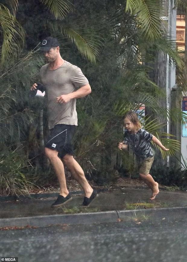 Ông bố phũ của năm: Cùng dầm mưa nhưng Thor Chris Hemsworth đội mũ đi giày, để con trai đầu trần chân đất - Ảnh 1.