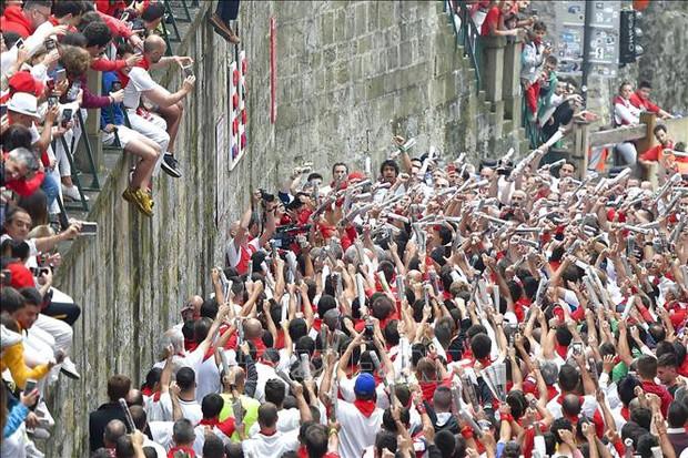 Hàng nghìn người quàng khăn đỏ cùng thắp nến, chia tay lễ hội chạy với bò tót - Ảnh 1.