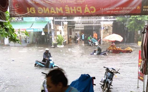 Clip: Vật lộn giữa dòng nước chảy xiết trên đường phố Sài Gòn, xe máy suýt bị cuốn trôi - Ảnh 2.