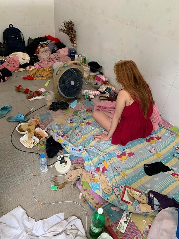 Hình ảnh cô gái mặc váy 2 dây ngồi nghịch điện thoại giữa căn phòng bừa bộn, ngập rác khiến nhiều người choáng váng - Ảnh 1.