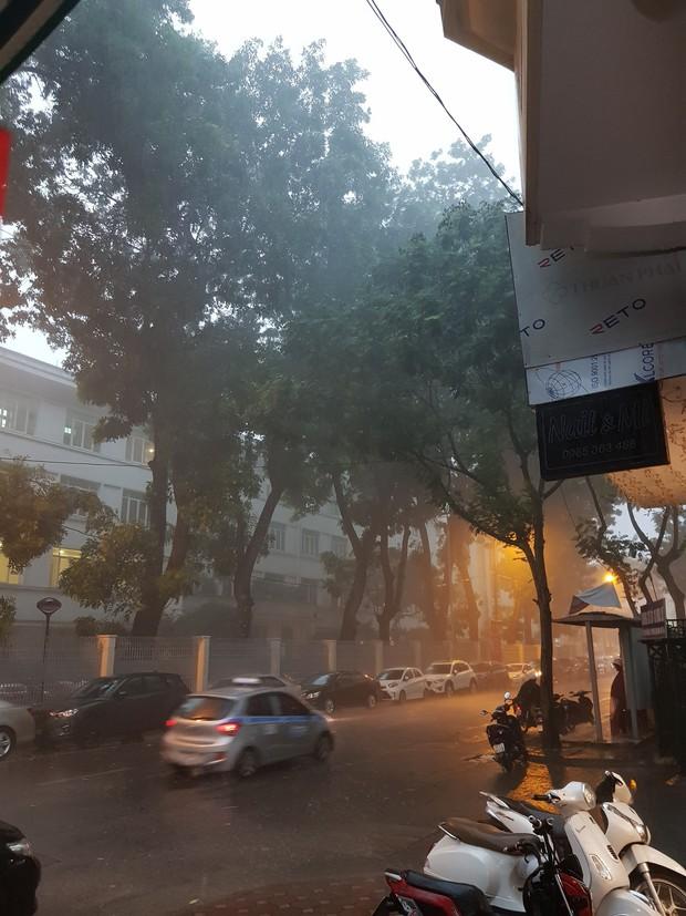 Giữa ban ngày mà Hà Nội bỗng tối đen như mực, người dân phải bật đèn di chuyển trên đường - Ảnh 10.