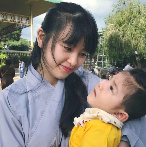 Hình ảnh em bé Lào Cai bụ bẫm đáng yêu trong bộ váy tím khi được bố nuôi bế khiến nhiều người chú ý - Ảnh 3.