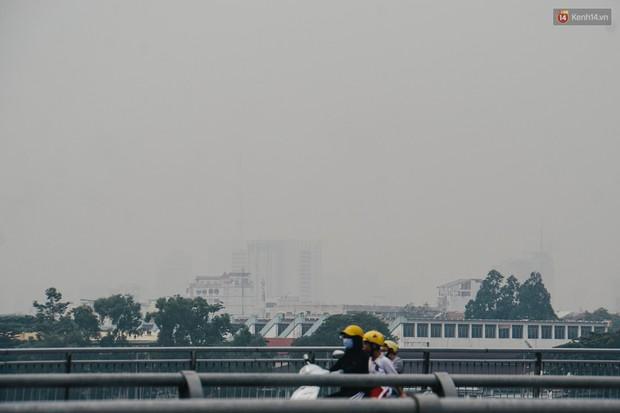Ảnh: Sài Gòn bị bao phủ một màu trắng đục từ sáng đến trưa, người dân cay mắt khi đi ngoài trời - Ảnh 4.