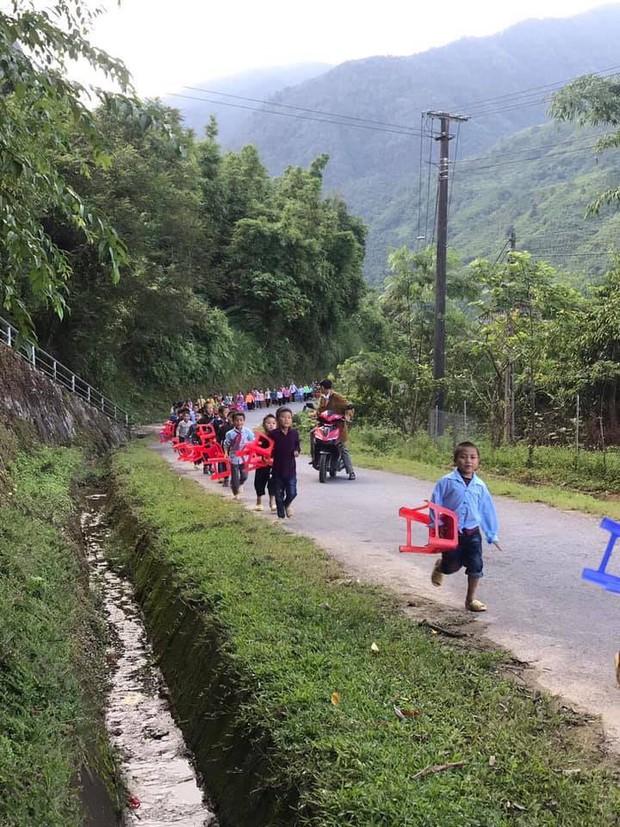Hình ảnh xúc động: Trẻ em vùng cao đi bộ hàng dài, xách ghế nhựa hân hoan đến điểm trường dự lễ khai giảng - Ảnh 1.