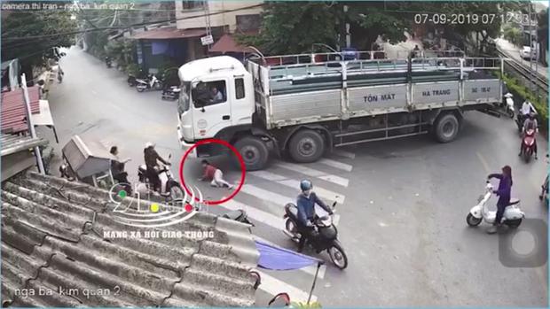 Hết hồn cảnh chiếc xe tải đang chầm chậm ôm cua thì 1 người phụ nữ chạy ra, chui dưới bánh xe để nằm - Ảnh 2.