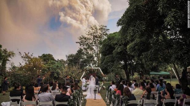 Mặc núi lửa phun trào dữ dội phía sau, đôi vợ chồng vẫn bình tĩnh tổ chức cho xong đám cưới đã rồi tính - Ảnh 2.
