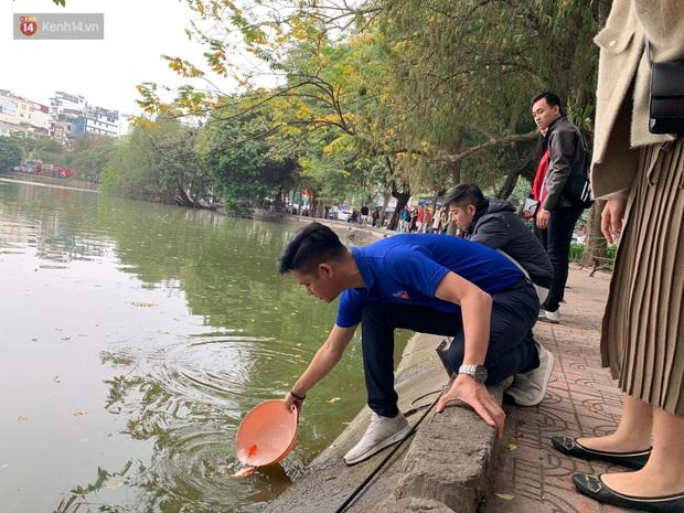 Dù nhóm tình nguyện viên hỗ trợ tiễn ông Công ông Táo về trời, một số người dân đứng trên cầu vẫn thản nhiên ném bát hương xuống sông - Ảnh 16.