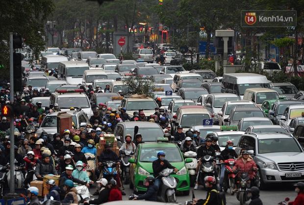 Đường phố Hà Nội tắc cứng và hỗn loạn trong chiều 23 Tết, người dân kiên nhẫn nhích từng chút một tranh thủ đi mua sắm - Ảnh 4.