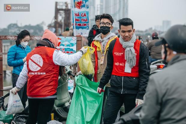 Dù nhóm tình nguyện viên hỗ trợ tiễn ông Công ông Táo về trời, một số người dân đứng trên cầu vẫn thản nhiên ném bát hương xuống sông - Ảnh 3.