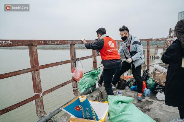 Dù nhóm tình nguyện viên hỗ trợ tiễn ông Công ông Táo về trời, một số người dân đứng trên cầu vẫn thản nhiên ném bát hương xuống sông - Ảnh 8.