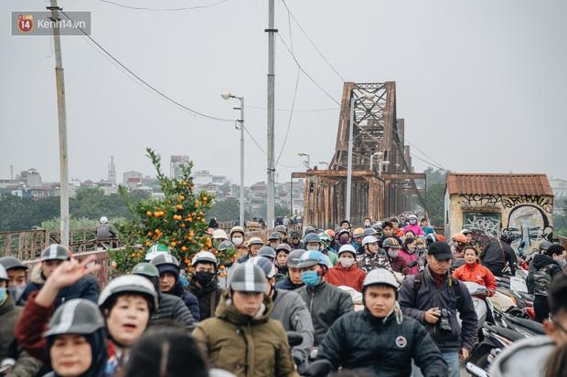 Dù nhóm tình nguyện viên hỗ trợ tiễn ông Công ông Táo về trời, một số người dân đứng trên cầu vẫn thản nhiên ném bát hương xuống sông - Ảnh 1.