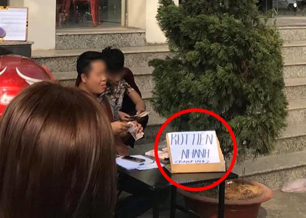 Góc cơ hội: Người đàn ông kê bàn mở dịch vụ rút tiền nhanh ngay cạnh cây ATM đang có hàng chục người chen chúc ngày giáp Tết - Ảnh 2.