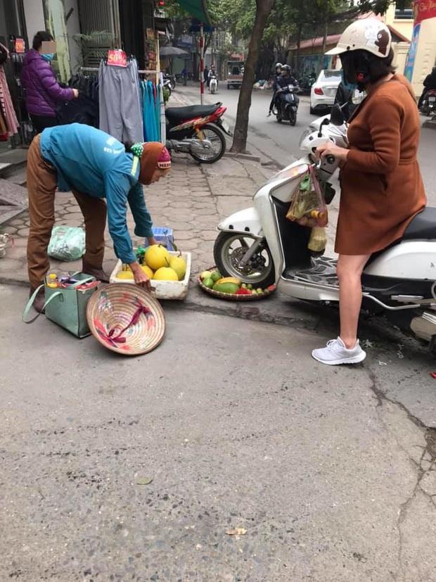 Phẫn nộ hình ảnh người phụ nữ mang bầu lái xe máy cán thẳng qua nia trái cây của cô bán hàng rong ven đường vì ngồi chắn trước cửa hàng - Ảnh 2.