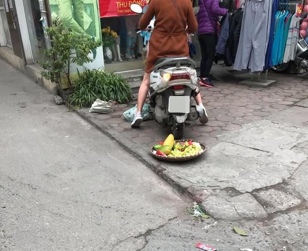 Phẫn nộ hình ảnh người phụ nữ mang bầu lái xe máy cán thẳng qua nia trái cây của cô bán hàng rong ven đường vì ngồi chắn trước cửa hàng - Ảnh 3.