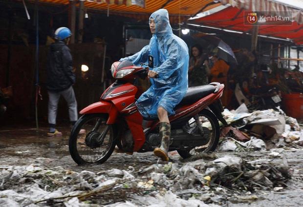 Chợ hoa Quảng An ngập trong rác, nhiều người vẫn tranh thủ đội mưa đi mua hoa Tết - Ảnh 4.