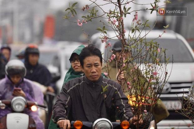 Chợ hoa Quảng An ngập trong rác, nhiều người vẫn tranh thủ đội mưa đi mua hoa Tết - Ảnh 14.