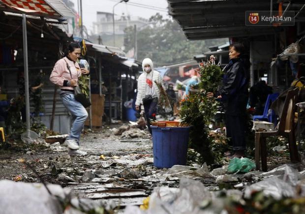 Chợ hoa Quảng An ngập trong rác, nhiều người vẫn tranh thủ đội mưa đi mua hoa Tết - Ảnh 1.