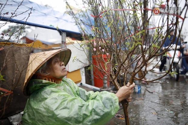 Chợ hoa Quảng An ngập trong rác, nhiều người vẫn tranh thủ đội mưa đi mua hoa Tết - Ảnh 5.