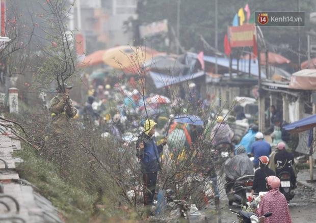 Chợ hoa Quảng An ngập trong rác, nhiều người vẫn tranh thủ đội mưa đi mua hoa Tết - Ảnh 10.