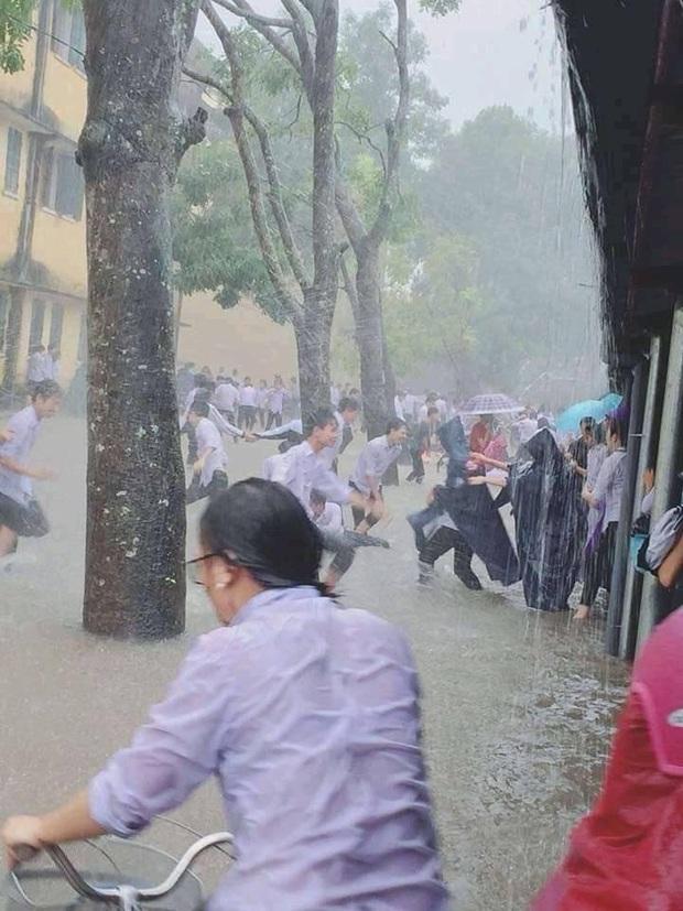 Mặc mưa ngập đến cả đầu gối, hàng chục học sinh vẫn vô tư chơi đùa dưới sân trường: Vui nhưng có an toàn? - Ảnh 2.