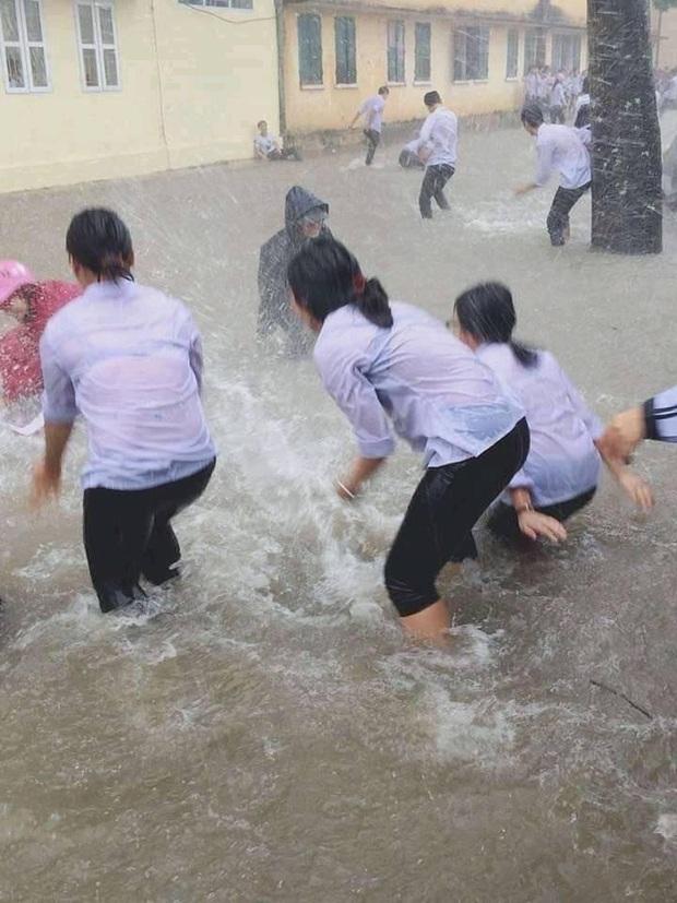 Mặc mưa ngập đến cả đầu gối, hàng chục học sinh vẫn vô tư chơi đùa dưới sân trường: Vui nhưng có an toàn? - Ảnh 1.