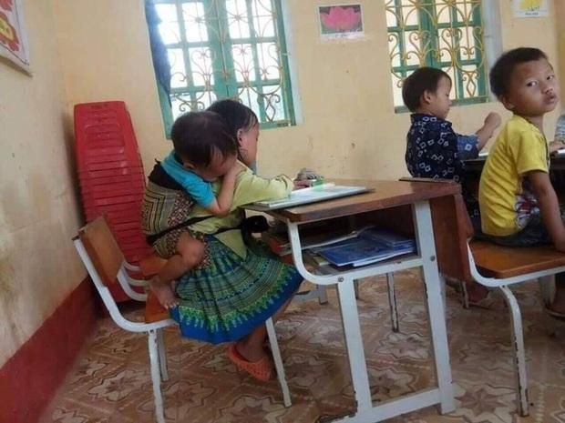 Bức ảnh chị 7 tuổi địu em 20 tháng tuổi đến lớp, chia nhau suất cơm trưa và câu chuyện phía sau - Ảnh 1.