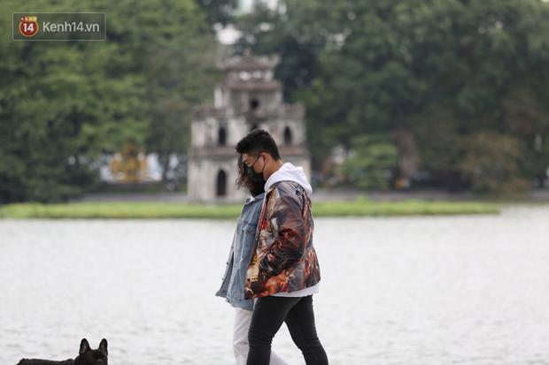Chùm ảnh: Nhiệt độ giảm xuống thấp nhất chỉ 19 độ C, người dân Hà Nội mang áo khoác ấm, co ro trong cái lạnh đầu mùa - Ảnh 7.