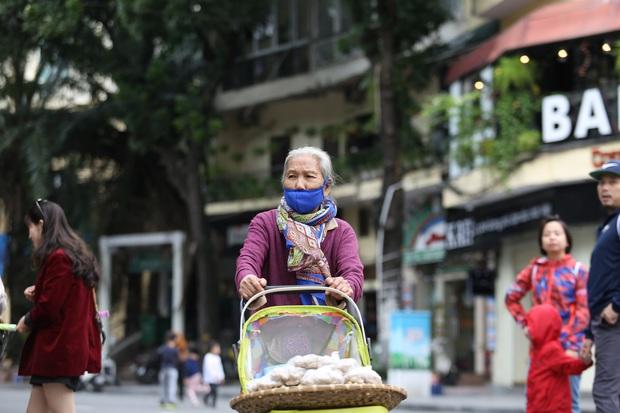 Chùm ảnh: Nhiệt độ giảm xuống thấp nhất chỉ 19 độ C, người dân Hà Nội mang áo khoác ấm, co ro trong cái lạnh đầu mùa - Ảnh 8.