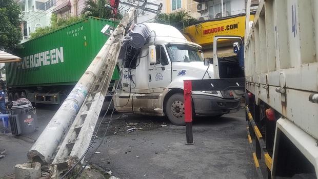 """TP.HCM: Xe container """"đại náo"""" đường phố, kéo ngã 2 cột điện, cả khu dân cư mất điện nguyên buổi sáng - Ảnh 1."""
