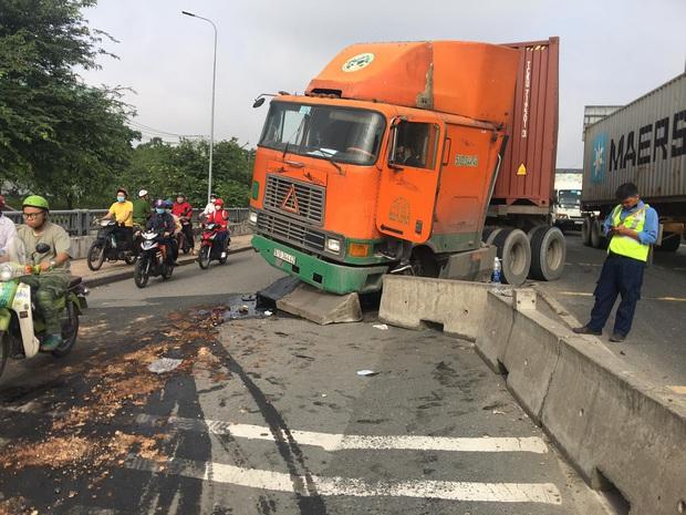 TP.HCM: Dầu nhớt tràn ra đường sau khi xe container ủi dải phân cách, nhiều người trượt ngã - Ảnh 1.