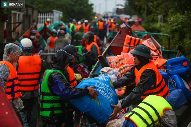 Ảnh: Người phụ nữ ở Quảng Bình lao ra dòng nước lũ xin đồ ăn cho mẹ già bật khóc khi được cứu hộ khỏi ghe lật - Ảnh 1.