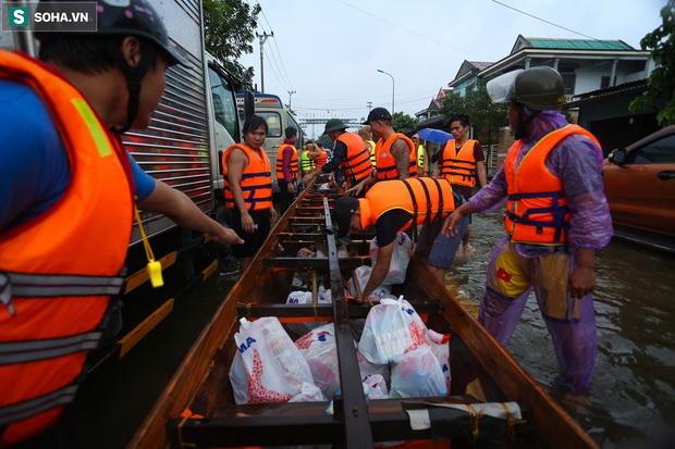 Ảnh: Người phụ nữ ở Quảng Bình lao ra dòng nước lũ xin đồ ăn cho mẹ già bật khóc khi được cứu hộ khỏi ghe lật - Ảnh 13.