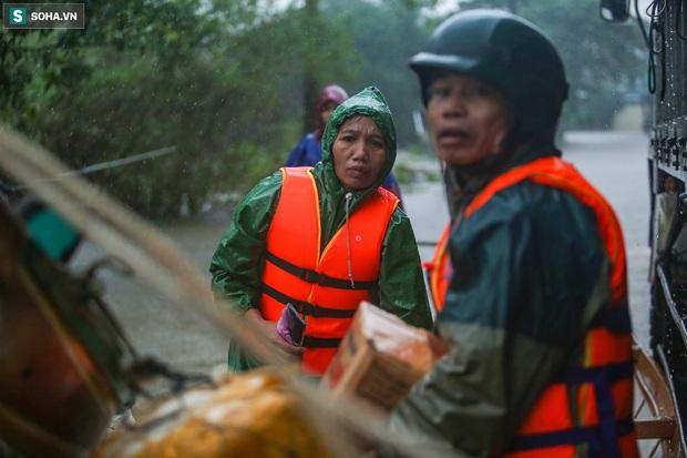 Ảnh: Người phụ nữ ở Quảng Bình lao ra dòng nước lũ xin đồ ăn cho mẹ già bật khóc khi được cứu hộ khỏi ghe lật - Ảnh 3.
