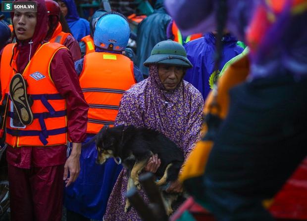 Ảnh: Người phụ nữ ở Quảng Bình lao ra dòng nước lũ xin đồ ăn cho mẹ già bật khóc khi được cứu hộ khỏi ghe lật - Ảnh 4.