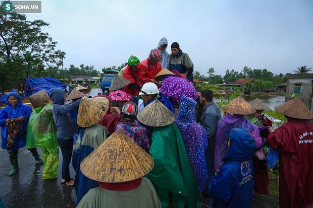 Ảnh: Người phụ nữ ở Quảng Bình lao ra dòng nước lũ xin đồ ăn cho mẹ già bật khóc khi được cứu hộ khỏi ghe lật - Ảnh 7.