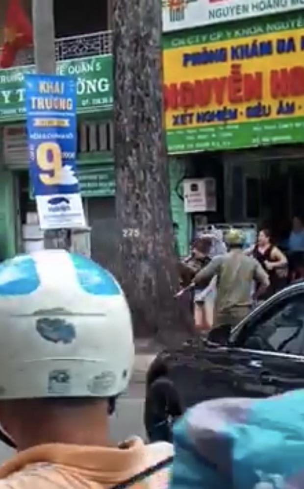 Dùng gậy sắt đập xe BMW, nam thanh niên bị nữ tài xế cầm ô rượt đuổi trên đường phố Sài Gòn - Ảnh 1.