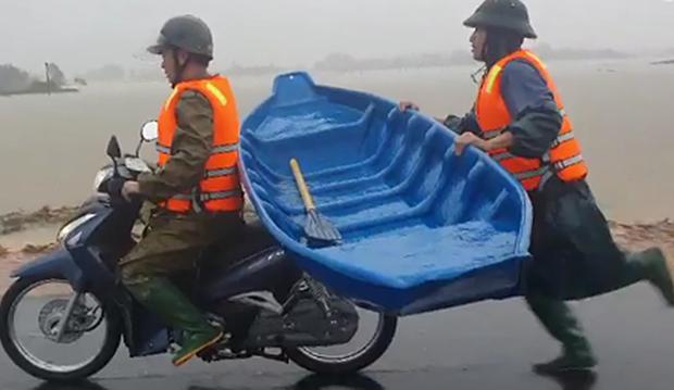 Clip: Chiến sĩ công an chạy bộ theo xe máy suốt 2km để giữ chiếc thuyền, nỗ lực cứu người dân bị mắc kẹt trong ngôi nhà lũ dâng cao hàng mét - Ảnh 2.
