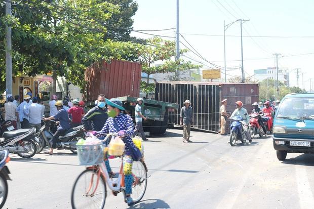 Kinh hoàng xe container nổ bánh mất lái kéo lê 5 xe máy, nhiều người bị thương - Ảnh 1.