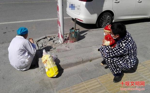 Người TQ rơi nước mắt vì cuộc đoàn tụ bên lề đường: Nữ y tá không dám gần chồng con, ngồi xổm ăn vội đồ ăn mẹ chồng chuẩn bị - Ảnh 1.