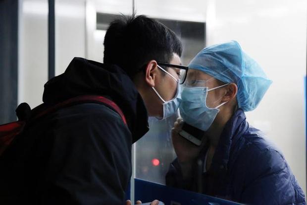 Khoảnh khắc nữ y tá chống dịch virus corona hôn bạn trai qua tấm kính cách ly: Chờ em ra ngoài, mình đi đăng kí kết hôn nhé! - Ảnh 1.
