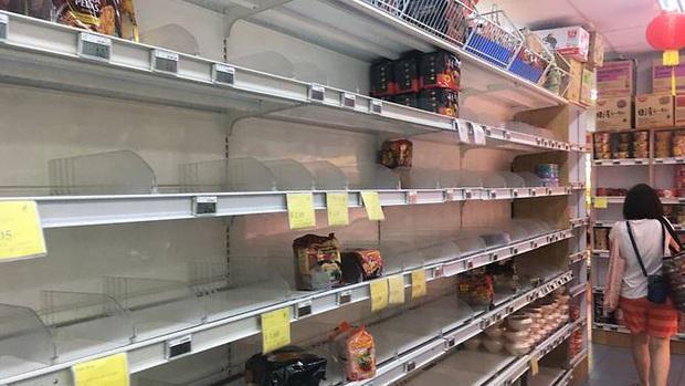 Singapore vừa nâng mức cảnh báo virus corona, người dân đã ùn ùn quét sạch nhu yếu phẩm tại hàng loạt siêu thị - Ảnh 2.