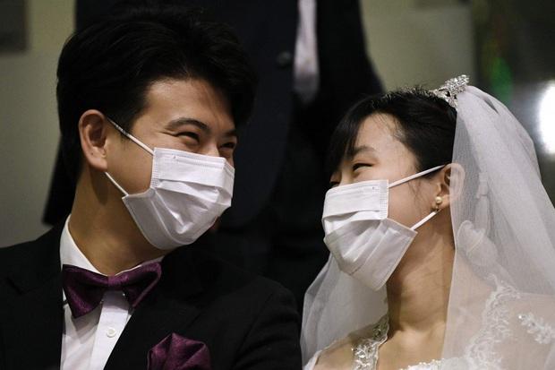 6000 cặp đôi kết duyên trong đám cưới tập thể ở Hàn Quốc giữa dịch viêm phổi: Người đeo khẩu trang kín mít, người vẫn bất chấp trao nụ hôn - Ảnh 1.