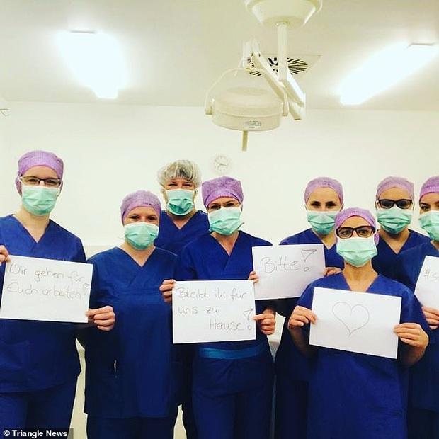 Các y bác sĩ trên toàn thế giới đồng loạt giơ cao thông điệp ý nghĩa: Chúng tôi đang làm việc vì các bạn còn các bạn hãy ở nhà vì chúng tôi - Ảnh 4.